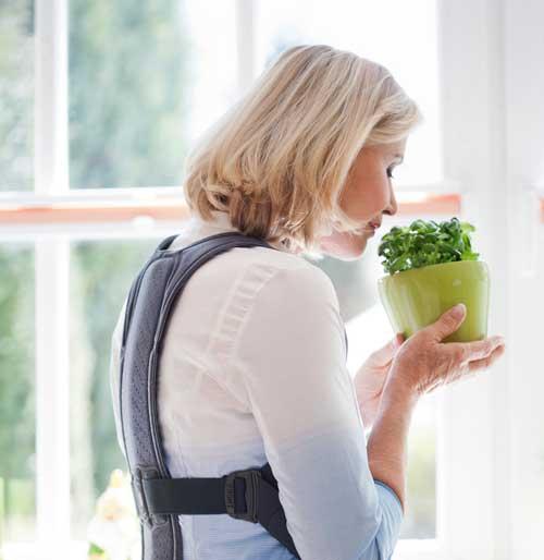 Frau riecht an einem Basilikum und trägt die Rückenorthse von medi bei Osteoporose