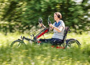 eine Frau auf einem Handbike in der Farbe Rot fährt durch eine Sommerwiese