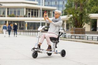 eine Frau auf dem Elektromobil ATTO ist in der Stadt unterwegs, das mobil ist klappbar und passt in den Kofferraum