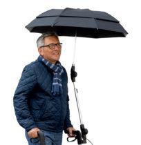 Ein Mann unter dem Regenschirm der an einem Rollator installiert ist