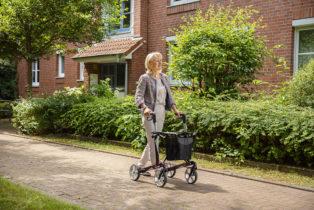 eine Frau beim Spaziergang im Sonnenschein mit einem dunkelroten Rollator aus leichter Carbonfaser