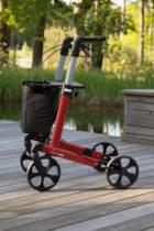 Carbonrollator in Rot mit montierter Einkaufstasche und bequemer Sitzfläche zum Ausruhen für Unterwegs