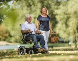 Elektrorollstuhl beim Spaziergang mit einer Frau im Park