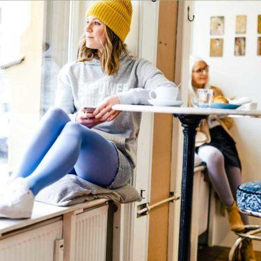 junge Frau sitzt auf einer Fensterbank und trägt Kompressionsstrümpfe in neuem Jeansblau